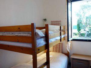 La chambre 'Saumon' n°2 avec des lits superposés est au contact du jardin